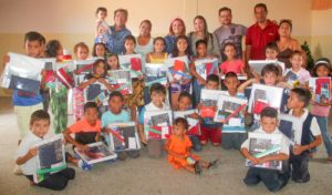 Children posing with donated school supplies