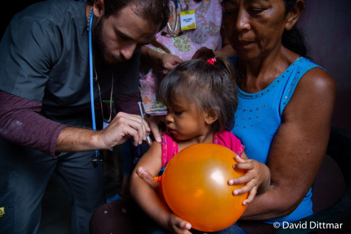Baby with an orange balloon getting a shot